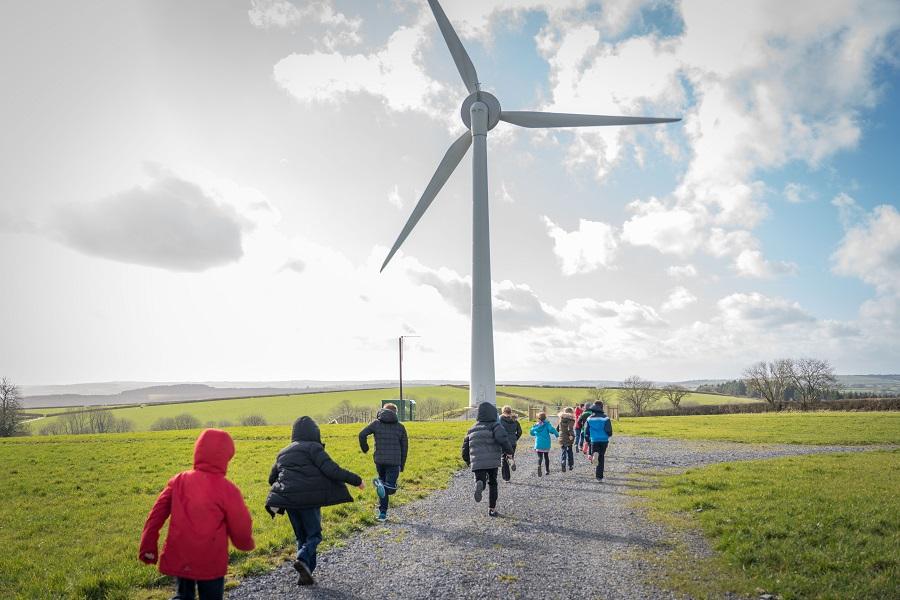 Children running towards wind turbine