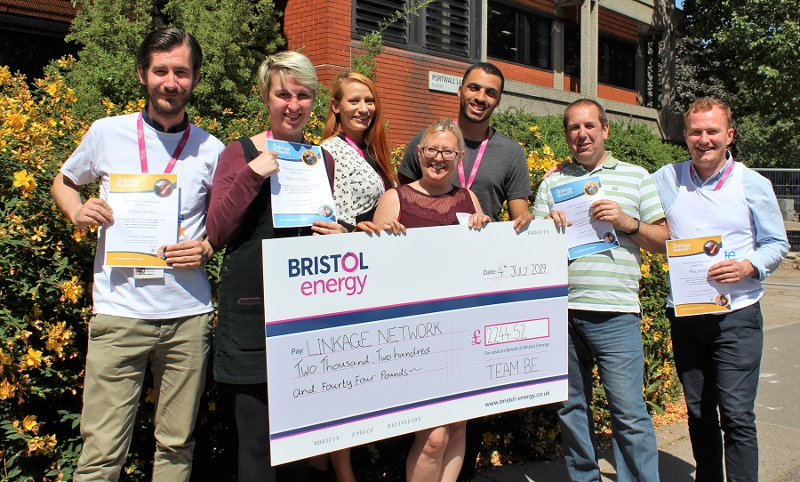 Bristol Energy and Link Age staff holding giant cheque