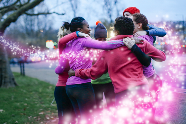 A group of runners dressed in pink celebrate creating positive energy for Bristol