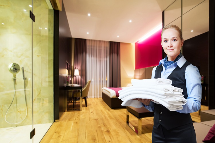Woman servicing hotel room in energy efficient hotel