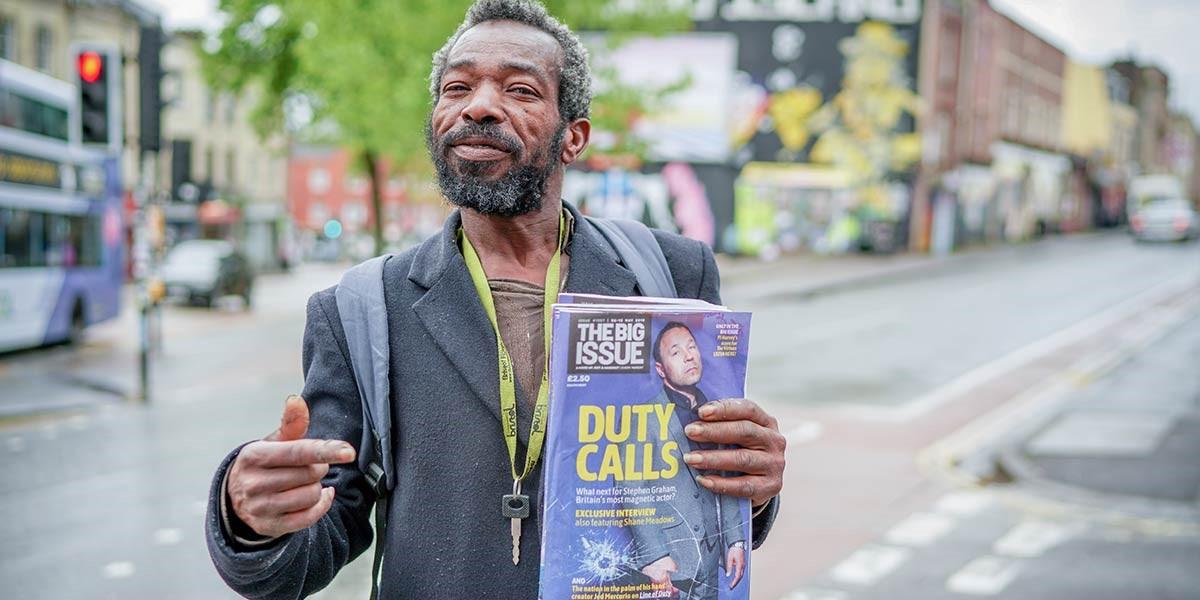 Big issue vendor standing on street